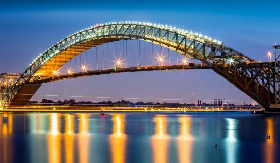 Bayonne Bridge at dusk. The Bayonne Bridge,the 5th longest steel arch bridge in the world, spans the Kill Van Kull and connects Bayonne, NJ with Staten Island, NY
