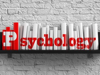 Psychology - Red Inscription on the Books on Shelf on the White Brick Wall Background. Education Concept.