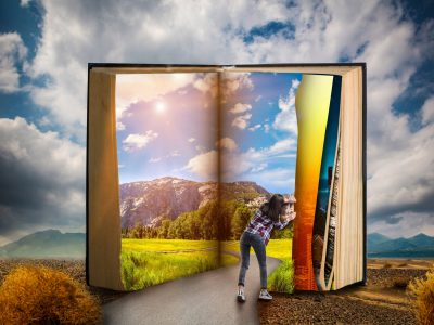 Little woman turns the page of large book, desert valley, blue sky with clouds on background, scale effect. Gaining knowledge and education, reading concept.